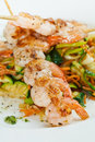 Shrimp on skewers on top of vegetables Stock Photo