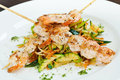 Shrimp on skewers on top of vegetables Stock Images