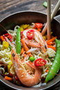 Shrimp with vegetables and noodles on old wooden table Stock Images
