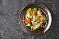 Shrimps and avocado salad on the vintage metal plate on the grey tablecloth Royalty Free Stock Photo