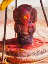 Shrine covered in vermillion to worship Goddess Kali. Red pigment powder on statue in Dhulikhel, Nepal