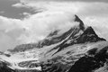 Shrouded peak jagged rocky alpine schreckhorn covered in snow and in clouds Stock Photos