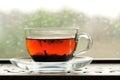 Shu puerh tea brewed in glass cup on window sill horizontal Stock Image