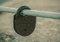 Shut up, old, worn, rusty, shabby padlock hanging on painted, worn, cut, pipe Royalty Free Stock Photo