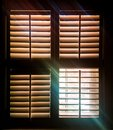 Shuttered window with one pane open letting through rays of light and a faint image of autumn leaves outside Royalty Free Stock Photo