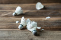 Shuttlecock with parts of its feathers scattered on wooden. Royalty Free Stock Photo