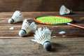 Shuttlecock and Racket with parts of its feathers scattered on wooden. Royalty Free Stock Photo