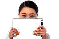 Shy corporate lady hiding her face smiling asian woman with tablet pc Stock Photos