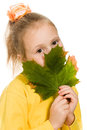 Shy girl with green maple leaf in his hand Stock Photo