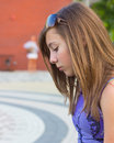 Shy girl lonely teenage looking down with another person in the distance Stock Photos