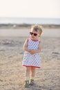 Shy girl in sunglasses walking on beach Stock Image
