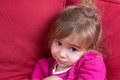 Shy little girl looking at the camera with big eyes as she snuggles down in a comfortable armchair Stock Images