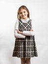 Shy schoolgirl in checkered dress against white background Royalty Free Stock Photo