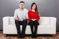 Shy woman and man sitting on sofa. First date. Royalty Free Stock Photo