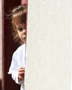 Shy young child hiding innocent girl in door frame Royalty Free Stock Photo