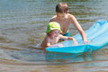 Sibling children having fun with inflatable blue pool lilo in summer lake outdoor are Royalty Free Stock Images