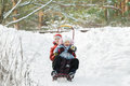 Sibling children having fun sliding down snowy hill during winter time Royalty Free Stock Photo