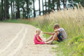 Sibling children playing in dust sitting on summer dirt road are Royalty Free Stock Photos