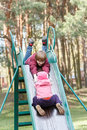 Sibling children are playing on playground slide made of metal together in old pine park Stock Photography