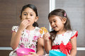 Sibling eating snacks two cute indian girls food asian or children enjoying traditional snack murukku living lifestyle at home Royalty Free Stock Image