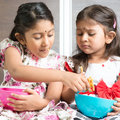 Sibling sharing foods indian girls food traditional snack murukku with each other asian or children living lifestyle at home Royalty Free Stock Image