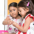 Sibling sharing snacks indian girls traditional snack murukku with each other asian or children eating food living lifestyle at Stock Photos