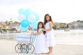 Siblings with carriage two sisters standing by a baby dozen of white and blue balloons Stock Photography