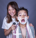 Siblings clowning with razor and cream a funny image of a boy showing his fear because sister has a Stock Image