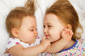 Siblings cuddling young sisters in bed Stock Photos