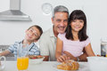 Siblings eating breakfast in kitchen together with dad Royalty Free Stock Photo