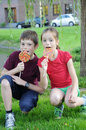 Siblings eating colorful big lollipops Royalty Free Stock Image