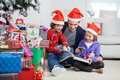Siblings and father reading book by christmas happy in santa hats while sitting presents at home Royalty Free Stock Photos