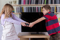 Siblings fighting desperatelly for the TV remote control in front of the televison Royalty Free Stock Photo