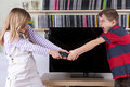 Siblings fighting over the remote control in front of the TV Royalty Free Stock Photo