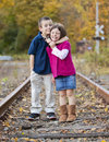 Siblings giving eachother a hug on the train tracks Royalty Free Stock Photography