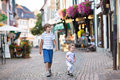 The siblings in a historical city centre cute school boy and his baby sister running and playing Stock Photography