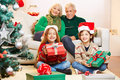 Siblings holding gifts at christmas two with grandmother and grandfather Royalty Free Stock Photo
