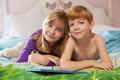 Siblings lying on bed toegther blonde haired sister and red haired brother happily in pajamas looking at camera Stock Photos