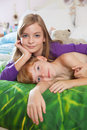 Siblings lying on bed toegther blonde haired sister and red haired brother happily in pajamas looking at camera Stock Images