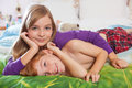 Siblings lying on bed toegther blonde haired sister and red haired brother happily in pajamas looking at camera Royalty Free Stock Photo