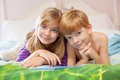 Siblings lying on bed toegther blonde haired sister and red haired brother happily in pajamas looking at camera Royalty Free Stock Photos