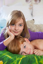 Siblings lying on bed toegther blonde haired sister and red haired brother happily in pajamas looking at camera Stock Photography