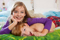 Siblings lying on bed toegther blonde haired sister and red haired brother laughing and happily in pajamas looking at camera Stock Photos