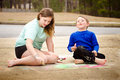 Siblings play with chalk drawing in drive way or sidewalk Royalty Free Stock Photos