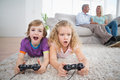 Siblings playing video game while parents sitting on sofa Royalty Free Stock Photo