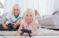 Siblings playing video games in the living room Royalty Free Stock Photography