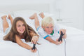 Siblings playing video games while they are lying on bed Royalty Free Stock Images