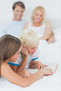 Siblings reading a book on the bed with their parents behind them Stock Photography