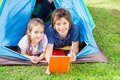 Siblings reading book in tent portrait of smiling at park Stock Photo