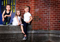 Siblings by red brick wall three happy young kids sitting together against a shallow depth of field copy space Royalty Free Stock Photos